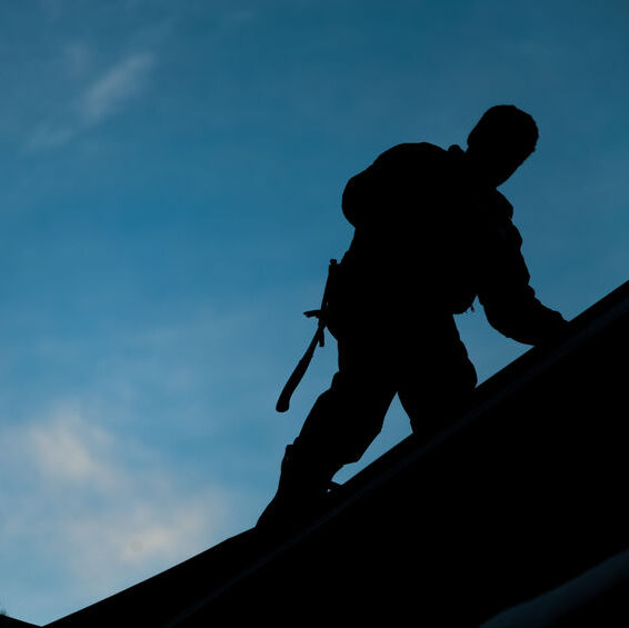Roofer working on commercial property silhouette