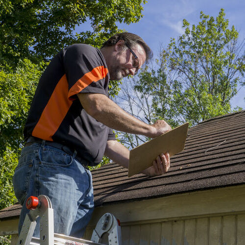 adjuster inspecting roof